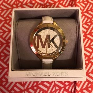Michael Kors watch with white band and gold face.